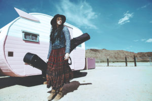 Gina Roode standing next to Trailer with guitar